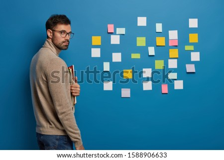 Studio shot of handsome serious male scholar looks seriously at camera, holds spiral notepads and textbooks, makes plans for day, wears transparent glasses isolated over blue wall with sticky notes #1588906633