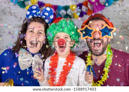 Happy disguised family celebrating carnival at home. Royalty-Free Stock Photo #1588917403
