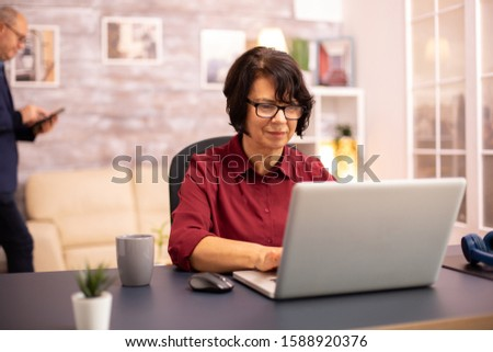 Old woman in her 60s using a modern laptop in her cozy house late in the evening #1588920376