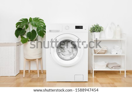 Interior of pastel colors laundry room with modern washing machine #1588947454