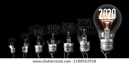 Group of shining and broken light bulbs in a shape of New Year 2020 and 2019 isolated on black background. #1588962958