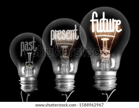 Large group of shining and dimmed light bulbs with fibers in a shape of Past, Present and Future words isolated on black background. Concept of Innovation, Development and Success #1588962967