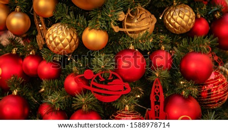 Christmas tree with gold bauble ornaments. Decorated Christmas tree closeup. Balls and illuminated garland with flashlights. New Year baubles macro photo with bokeh. Winter holiday light decoration #1588978714
