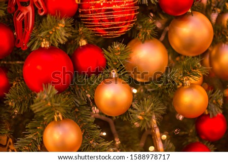 Christmas tree with gold bauble ornaments. Decorated Christmas tree closeup. Balls and illuminated garland with flashlights. New Year baubles macro photo with bokeh. Winter holiday light decoration #1588978717