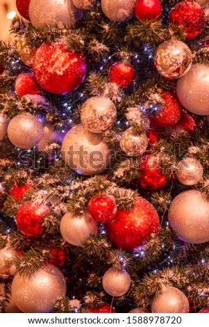 Christmas tree with gold bauble ornaments. Decorated Christmas tree closeup. Balls and illuminated garland with flashlights. New Year baubles macro photo with bokeh. Winter holiday light decoration #1588978720