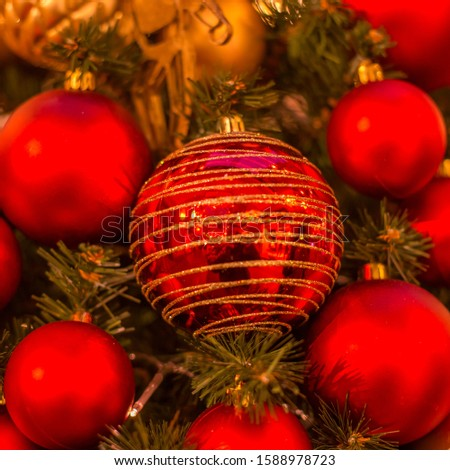 Christmas tree with gold bauble ornaments. Decorated Christmas tree closeup. Balls and illuminated garland with flashlights. New Year baubles macro photo with bokeh. Winter holiday light decoration #1588978723