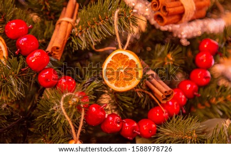 Christmas tree with gold bauble ornaments. Decorated Christmas tree closeup. Balls and illuminated garland with flashlights. New Year baubles macro photo with bokeh. Winter holiday light decoration #1588978726