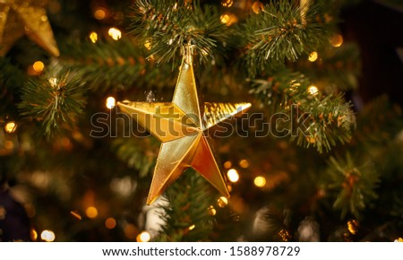 Christmas tree with gold bauble ornaments. Decorated Christmas tree closeup. Balls and illuminated garland with flashlights. New Year baubles macro photo with bokeh. Winter holiday light decoration #1588978729