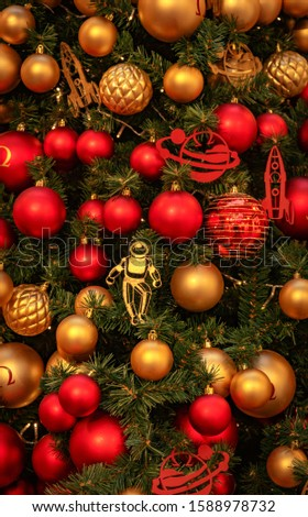 Christmas tree with gold bauble ornaments. Decorated Christmas tree closeup. Balls and illuminated garland with flashlights. New Year baubles macro photo with bokeh. Winter holiday light decoration #1588978732