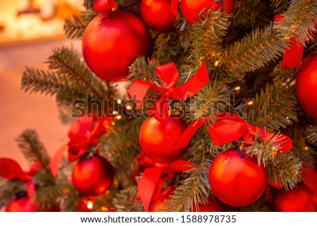 Christmas tree with gold bauble ornaments. Decorated Christmas tree closeup. Balls and illuminated garland with flashlights. New Year baubles macro photo with bokeh. Winter holiday light decoration #1588978735
