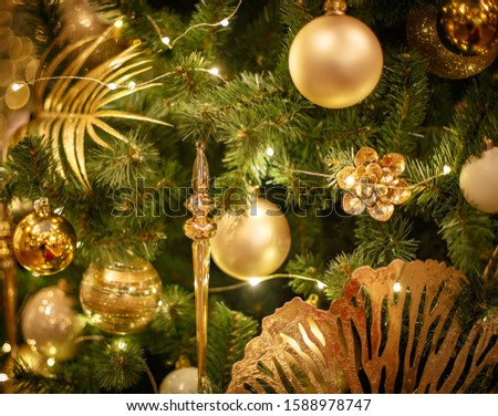 Christmas tree with gold bauble ornaments. Decorated Christmas tree closeup. Balls and illuminated garland with flashlights. New Year baubles macro photo with bokeh. Winter holiday light decoration #1588978747