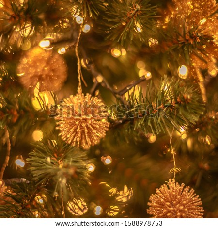 Christmas tree with gold bauble ornaments. Decorated Christmas tree closeup. Balls and illuminated garland with flashlights. New Year baubles macro photo with bokeh. Winter holiday light decoration #1588978753