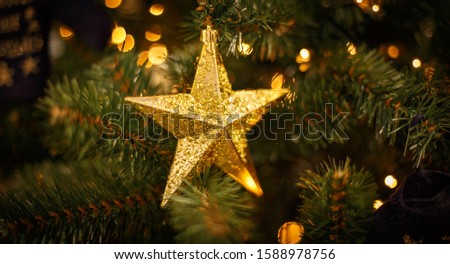 Christmas tree with gold bauble ornaments. Decorated Christmas tree closeup. Balls and illuminated garland with flashlights. New Year baubles macro photo with bokeh. Winter holiday light decoration #1588978756