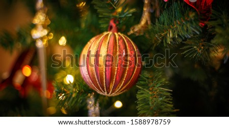 Christmas tree with gold bauble ornaments. Decorated Christmas tree closeup. Balls and illuminated garland with flashlights. New Year baubles macro photo with bokeh. Winter holiday light decoration #1588978759