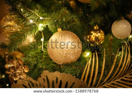 Christmas tree with gold bauble ornaments. Decorated Christmas tree closeup. Balls and illuminated garland with flashlights. New Year baubles macro photo with bokeh. Winter holiday light decoration #1588978768