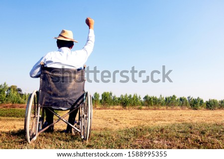Young disabled man with field background.He is sitting on wheelchair and raising hand  up .He is looking into sky.despair,lonely,hope.Photo concept depression and Patient. #1588995355
