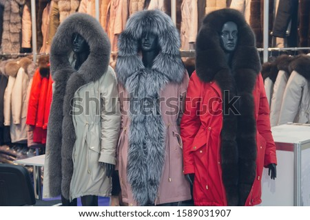 Women's mannequins in winter clothes in the shop window. Fashion #1589031907