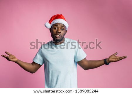 Waist up shot of bewildered african american man spreading hands, wearing Santa hat, t shirt, looking at the camera puzzled, doesn't understand what happened, isolated on pink background. #1589085244
