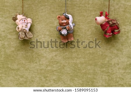 Christmas toys, a snowman, a bear and a deer, suspended from above closer to the center, large on a green plush. #1589095153