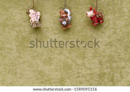 Christmas toys, snowman, teddy bear and deer, suspended at the top, on a green plush background. #1589095156