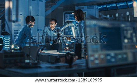 Diverse Team of Engineers with Laptop and a Tablet Analyse and Discuss How a Futuristic Robotic Arm Works and Moves a Metal Object. They are in a High Tech Research Laboratory with Modern Equipment. Royalty-Free Stock Photo #1589189995