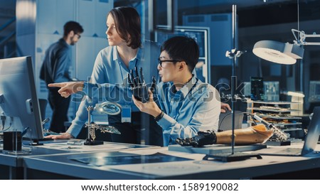 Technological Prosthetic Robot Arm is Tested by Two Professional Development Engineers in a High Tech Research Laboratory with Modern Futuristic Equipment. Man and Female Compare Data on a PC #1589190082