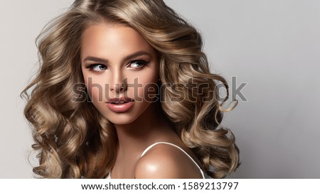 Beauty brunette girl with long  and   shiny wavy  hair .  Beautiful   woman model with curly hairstyle . Perm, trichology and care Royalty-Free Stock Photo #1589213797