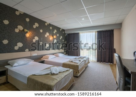Bright and cozy modern hotel bedroom with comfortable bed and nice wallpaper. #1589216164