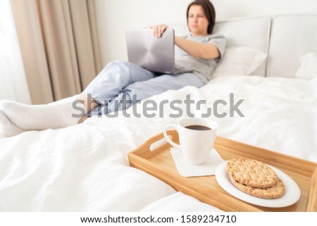 Woman in bed with laptop and breakfast #1589234710