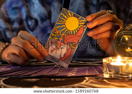 Fortune teller of hands holding THE SUN card and tarot cards on table near burning candles in candle light.Tarot cards spread on table with crystal ball.Forecasting concept. #1589260768