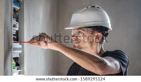 Man, an electrical technician working in a switchboard with fuses. Installation and connection of electrical equipment. Professional with tools in hand. concept of complex work, space for text. #1589295124