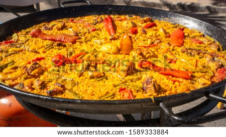 Close up photo of a traditional Paella in Valencia cooking in a typical iron cast big pan on the street during a paella competition in Cullera, Spain. Traditional Spanish Mediterranean food and diet. #1589333884