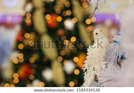 decorative dove Christmas tree toy and garland lights bokeh illumination winter holidays fairy tale happy time concept wallpaper pattern picture for some advertising with empty copy space for text