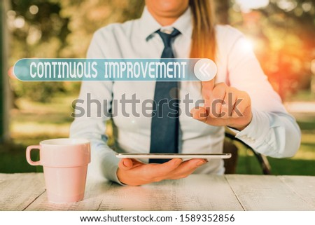 Handwriting text writing Continuous Improvement. Concept meaning ongoing effort to improve products or processes Female business person sitting by table and holding mobile phone. #1589352856