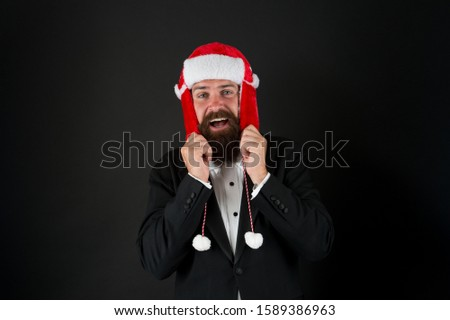 This hat warms his ears. Happy businessman wear santa hat. Bearded man smile in hat with earflaps and faux fur. Fashion accessory for Christmas. Warm and stylish trapper hat for santa party. #1589386963