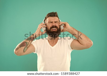 Stylish and handsome music lover. Man in headphones. Free online music sources all work little bit differently and have many different features. Music chart. Mature hipster with beard listening music. #1589388427