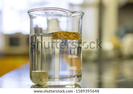 Density of 2 different materials in a beaker. One object floating and one sinking. Royalty-Free Stock Photo #1589395648