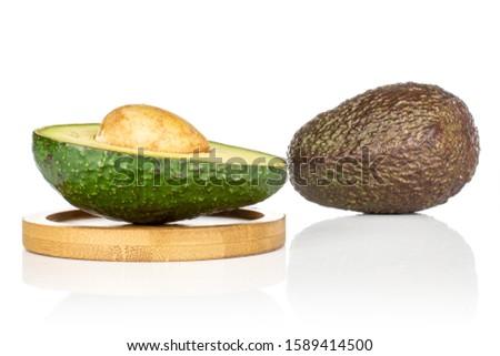 Group of one whole one half of fresh green avocado on round bamboo coaster isolated on white background #1589414500