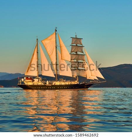Sailing ship with sails at sunset. Cruises Travel. Yachting #1589462692