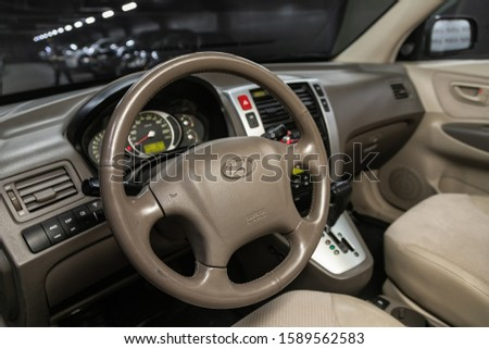 Novosibirsk, Russia – October 26, 2019:  Hyundai Tucson,  Beige luxury car Interior - dashboard, player, steering wheel with logo and buttons, speedometer and tachometer #1589562583