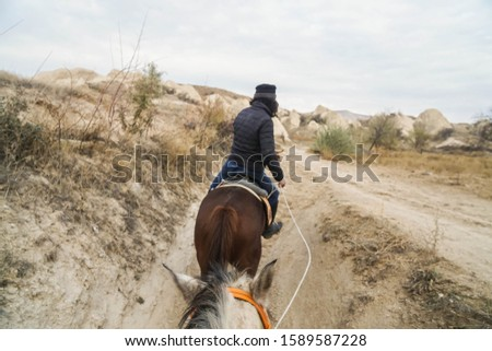 selective focus on white horse head and hair on horse riding guided by local tour guide in Cappadocia, Turkey #1589587228