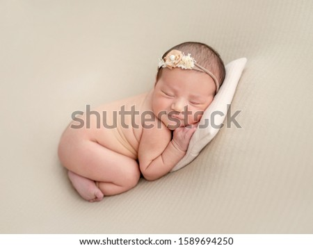 Naked innocent newborn with diadem on her head #1589694250