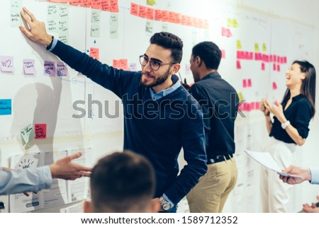 Multiethnic executives in formal wear discussing about wall with colorful stickers and working on creative business project together at office  #1589712352