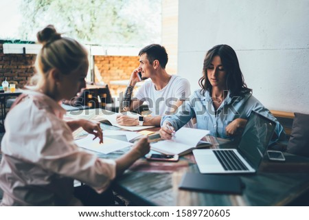 Friends sitting at table with notebooks and laptop with blank screen while focused young women discussing written plan and man talking on smartphone #1589720605