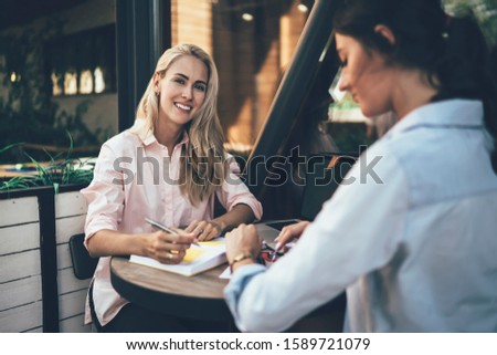 Young blonde writing in notebook smiling at camera sitting at terrace table with ethnic female colleague checking time on watch #1589721079