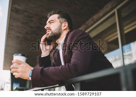 Serious male entrepreneur in formal wear concentrated during mobile phone conversation during coffee break, handsome prosperous man lawyer making smartphone call talking about case on break