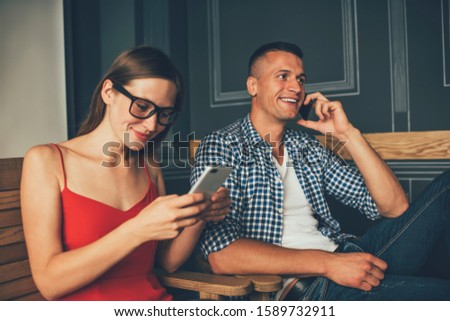 Young female employee in glasses text messaging on cellphone and sitting next to casually dressed male colleague talking on cellphone #1589732911