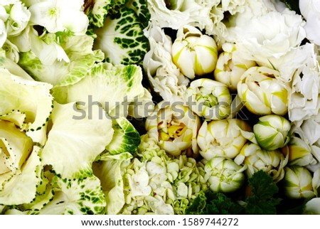 Still life macro photography of white floral arrangement consisting of roses, geraniums, tulips, kale flowers, hydrangeas, camellias and hypericum berries