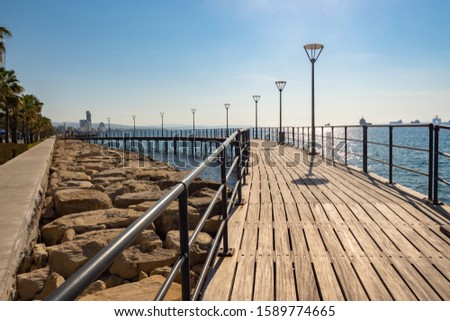Cyprus. Limassol. Wooden promenade on the shores of the Mediterranean Sea. Walks along the promenade of Cyprus. Cityscape of Limassol. Mediterranean cruise. Travels to the island of Cyprus. Royalty-Free Stock Photo #1589774665