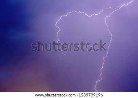 lightning in the night blue-lilac sky two long curving curves. bright flash in the sky #1589799196
